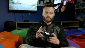 供以人员有效地打与控制杆的计算机游戏 游戏玩家在运转的电视背景中坐微薄的椅子  股票录像