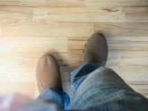 供以人员有棕色鞋子的佩带的蓝色牛仔裤在木木条地板 免版税库存照片