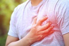 供以人员有胸口痛-心脏攻击户外 或者重的锻炼造成身体冲击心脏 库存图片