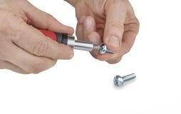 供以人员有螺丝刀的手和螺丝或者螺栓 免版税库存照片