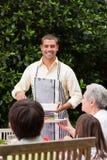 供以人员服务他的母亲在表 免版税库存图片