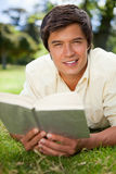 供以人员朝前看,当读书时,他在草位于 免版税图库摄影