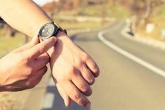 供以人员检查在手表的手时间在路边 图库摄影