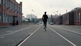 供以人员沿一条老市区街道的赛跑 回到视图 在对成功和到达目标的途中 对比射击 股票录像