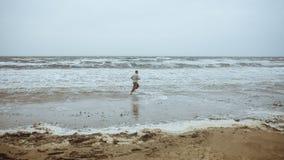 供以人员沿海滨的赛跑在多暴风雨的天气 免版税库存照片