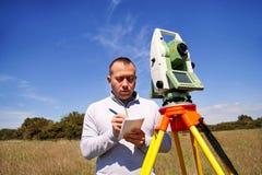 供以人员测量员在工作和使用总驻地 免版税库存照片