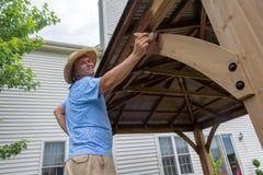 供以人员涂清漆在他的露台的一个木眺望台 库存图片
