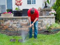 供以人员清洗一个肮脏的格栅的压力从BBQ 免版税库存图片