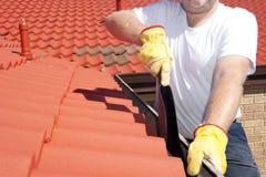 供以人员清洗红色屋顶的季节性天沟 免版税库存图片