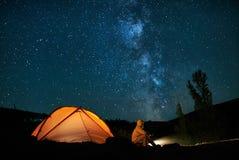 供以人员游人靠近他的阵营帐篷在晚上 库存图片