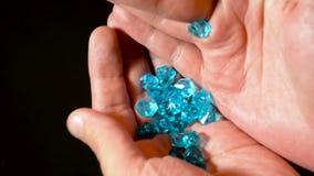 供以人员滚动的手并且打旋蓝色金刚石或宝石和检查质量 股票视频