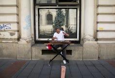 供以人员演奏在国家银行,布加勒斯特前面的洋琴 免版税库存图片