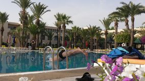 供以人员潜水在旅馆游泳池的水中,慢动作 股票视频