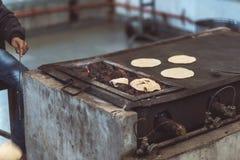 供以人员烹调印地安平的面包,称薄煎饼和烤它在活火焰 被定调子的图象,葡萄酒过滤器 图库摄影