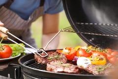 供以人员烹调鲜美肉和菜在烤肉格栅户外 免版税库存图片