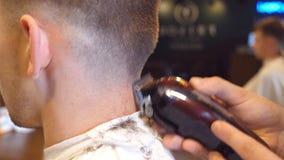 供以人员理发师切口头发在男性客户的脖子有飞剪机的在理发店 发型过程 慢动作关闭 影视素材