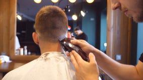 供以人员理发师男性客户的切口头发有飞剪机的在理发店 发型过程 慢动作关闭 股票视频
