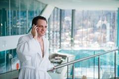 供以人员用途手机在的豪华旅馆温泉靠近游泳池 免版税图库摄影