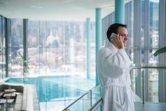 供以人员用途手机在的豪华旅馆温泉靠近游泳池 库存照片