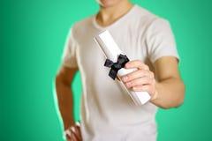 供以人员白皮书手中举行的纸卷与一把黑弓的在a 免版税库存图片