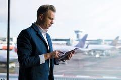 供以人员看片剂,当站立在机场休息室时 免版税库存照片