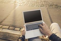 供以人员研究他的膝上型计算机的商人自由职业者户外 免版税库存图片