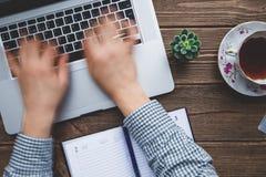 供以人员研究在木书桌安置的膝上型计算机 免版税图库摄影