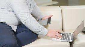 供以人员研究数字式片剂和膝上型计算机的图表设计师 股票录像