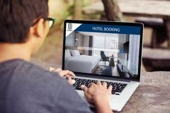 供以人员研究膝上型计算机,搜寻寄宿使用网上网站服务,预定在网站上的一家旅馆 库存图片