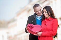 供以人员给一个心形的礼物他的女朋友 图库摄影