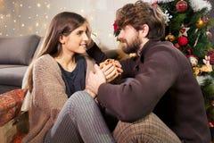 供以人员给圣诞节礼物微笑在爱中景的女朋友 库存图片