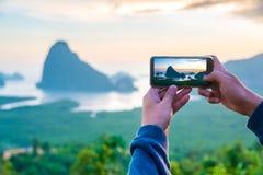 供以人员被拍摄的日落在与这个智能手机的Phang Nga海湾, Phang Nga,泰国 库存照片