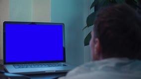 供以人员观看在蓝色关键笔记本计算机屏幕在厨房靠近火炉 股票视频
