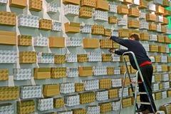 供以人员解决在墙壁上的纸板箱, 图库摄影