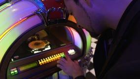 供以人员设法选择在老自动电唱机滴下的硬币的好歌曲和推挤钥匙 股票视频