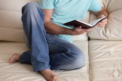 供以人员读举行在他的手上的老精装书笔记本,在白色长沙发 国内生活方式 登记概念教育查出的老 图库摄影