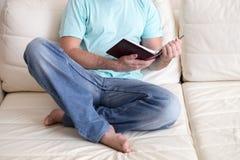 供以人员读举行在他的手上的老精装书笔记本,在白色长沙发 国内生活方式 登记概念教育查出的老 免版税库存照片