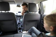 供以人员谈话在汽车的手机 库存照片