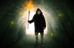供以人员走与在一个黑暗的隧道的灼烧的大烛台 免版税图库摄影