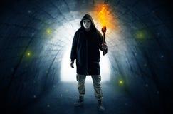 供以人员走与在一个黑暗的隧道的灼烧的大烛台 图库摄影