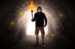 供以人员走与在一个黑暗的隧道的灼烧的大烛台 免版税库存图片
