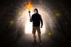 供以人员走与在一个黑暗的隧道的灼烧的大烛台 库存照片