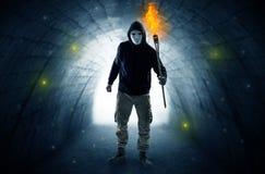 供以人员走与在一个黑暗的隧道的灼烧的大烛台 免版税库存照片