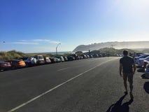 供以人员走沿路的边有许多停放的汽车的,他 库存图片
