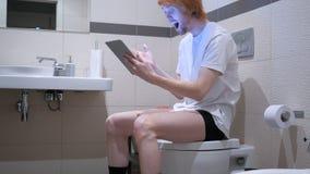 供以人员起反应对在片剂个人计算机的成功在洗手间,洗脸台 免版税库存图片
