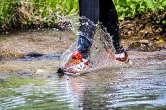 供以人员跑在山的足迹,横渡小河 库存图片