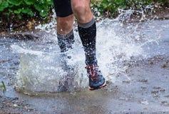 供以人员跑在山的足迹,横渡小河 免版税库存照片