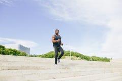 供以人员跑阶梯步级,训练的非洲人室外,当跑步步时 免版税图库摄影