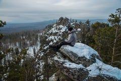 供以人员远足者坐岩石在山上面,冬天冒险 图库摄影