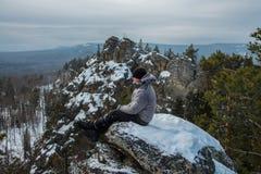 供以人员远足者坐岩石在山上面,冬天冒险 库存图片